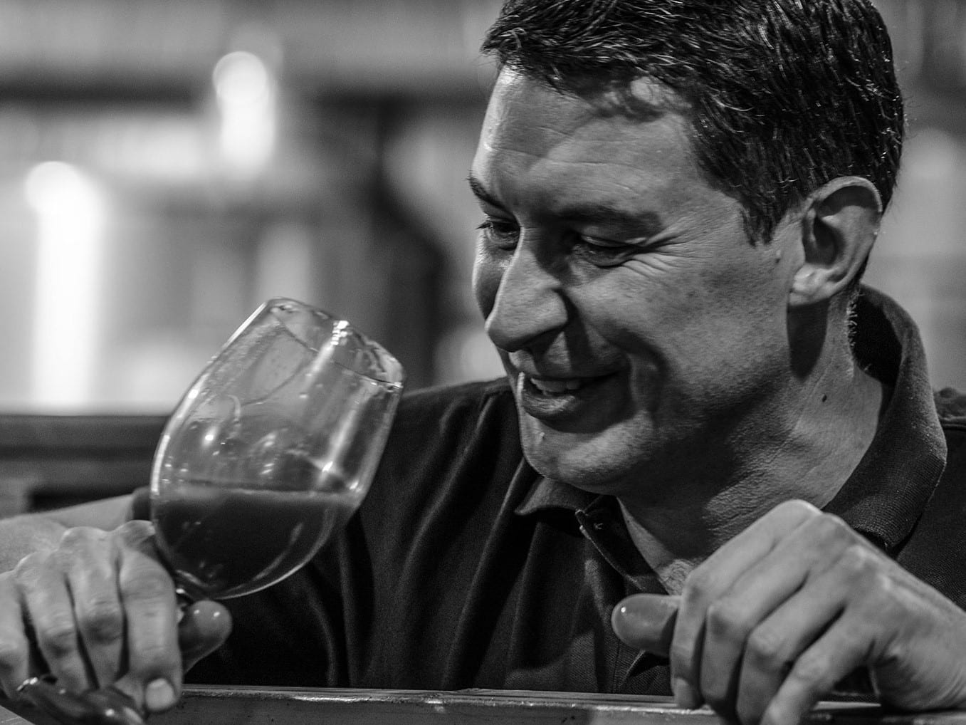 Black and white photo of Scott tasting a wine